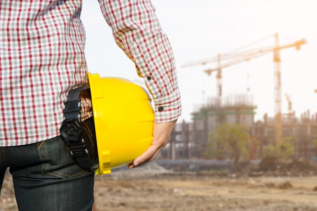 hand-s-engineer-worker-holding-yellow-safety-helmet-with-building-on-site-background_1439-9