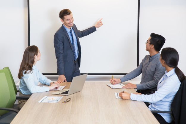 happy-business-coach-consulting-team-in-boardroom_1262-2128