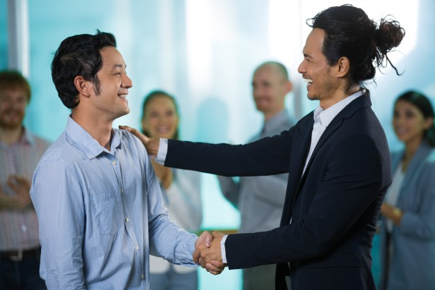 happy-colleagues-talking-while-shaking-hands_1262-5141