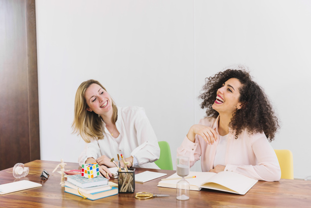 laughing-women-studying-at-table_23-2147774779