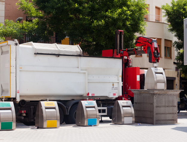 recycling-truck-picking-up-bin-at-city_1398-4392