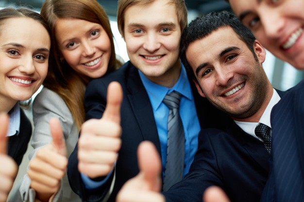 smiling-businessteam-holding-their-thumbs-up_1098-796